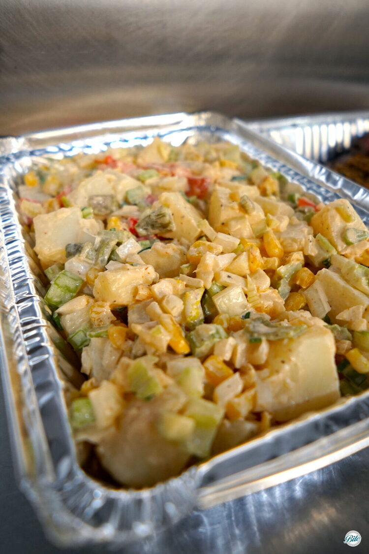 Grilled corn, red and green peppers, chopped potatoes with a bit of a kick. Family-style packaged in aluminum for meal service.