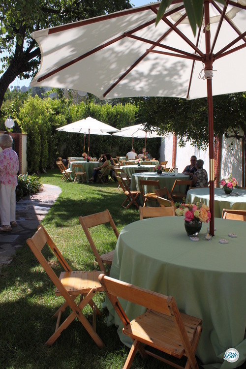 Tables with green linen and wooden chairs set up in backyard with umbrellas