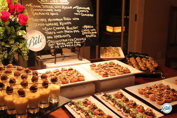Close-up of crostini bar display including flowers, chalkboard sign, mango lassi shots, assorted crostini, and yorkshire pudding bites