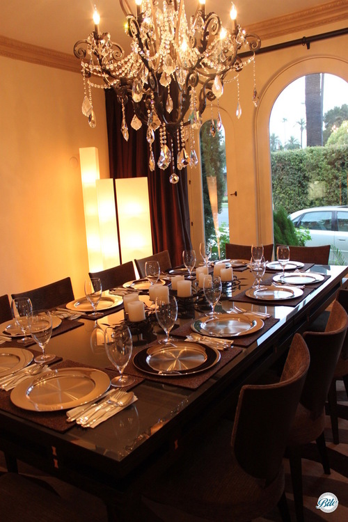 Chandelier over dinner table at elegant party.  Seating at small table for plated meal.