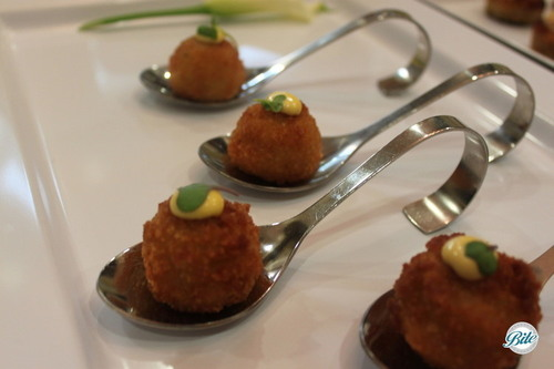 Tray passed tasting spoons of vegetable croquettes topped with saffron aioli and micro green garnish