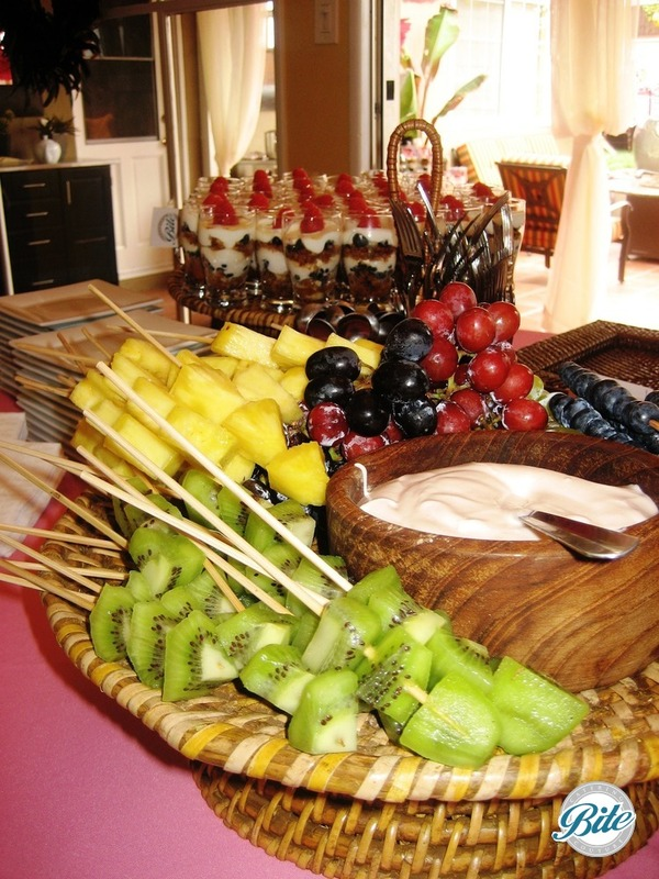 Kiwi, pineapple, and blueberry skewers with grapes and yogurt dipping sauce, also shown with mini granola and raspberry yogurt parfaits.