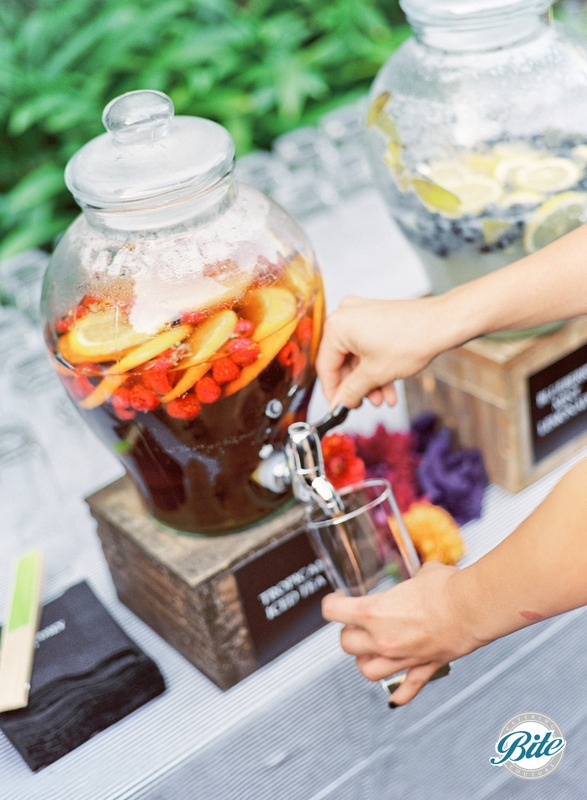 Beverage display for outdoor ceremony: agave sweetened iced tea with fresh fruit, along with blueberry and lemon infused water on rustic display with wood crates