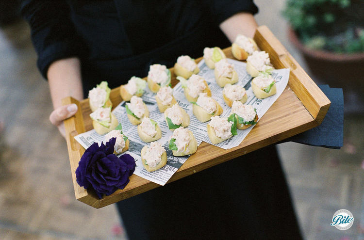 Lobster roll appetizer tray passed with herb garish and floral tray garnish on mini newspaper