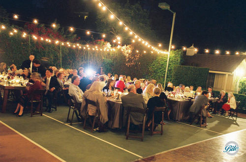 Guests at outdoor reception, eating under bistro lighting for ambiance