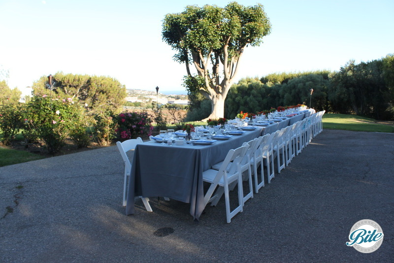 Long banquet style seating for outdoor event with the skyline as back drop. The table has grey linens with white folding chairs and white china for plated dinner.