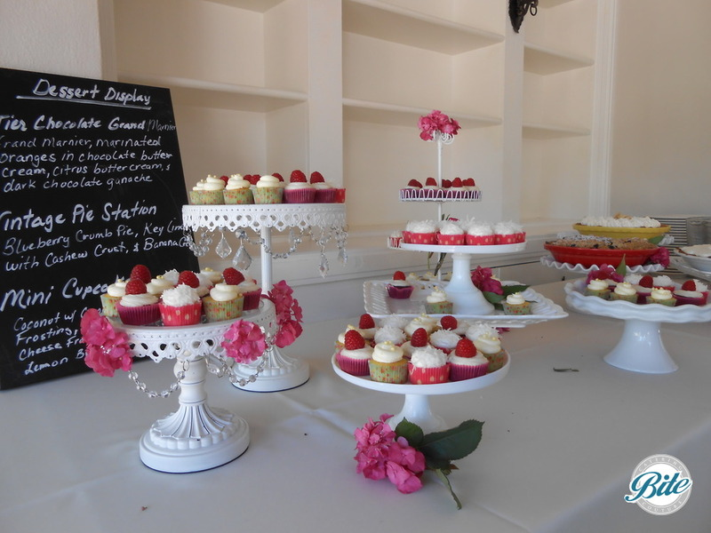Mini cupcakes and vintage pie station for wedding dessert buffet on tiered displays with fresh flowers
