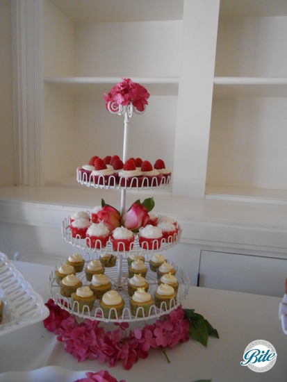 Mini cupcakes on display for wedding on shabby chic display with pink roses and hydrangeas
