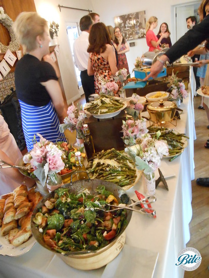 Wedding buffet dinner with artisan bread, seasonal salad, and asparagus with shaved Parmesan on rustic display