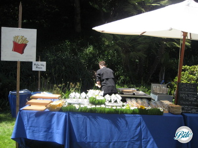 Grill action station at outdoor wedding reception with BBQ and truffle fries served in paper cones