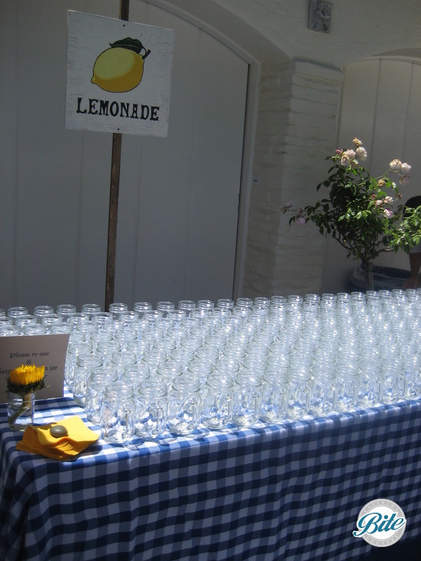 Mason jar display on picnic table for fresh lemonade at outdoor wedding reception