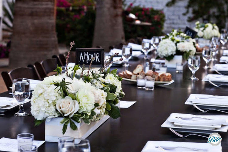 Tablescape with family style set up, dark wood tables, and ivory centerpieces
