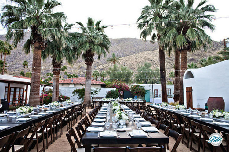 Palm springs wedding reception with banquet style seating outdoors with palam trees, and bistro lighting