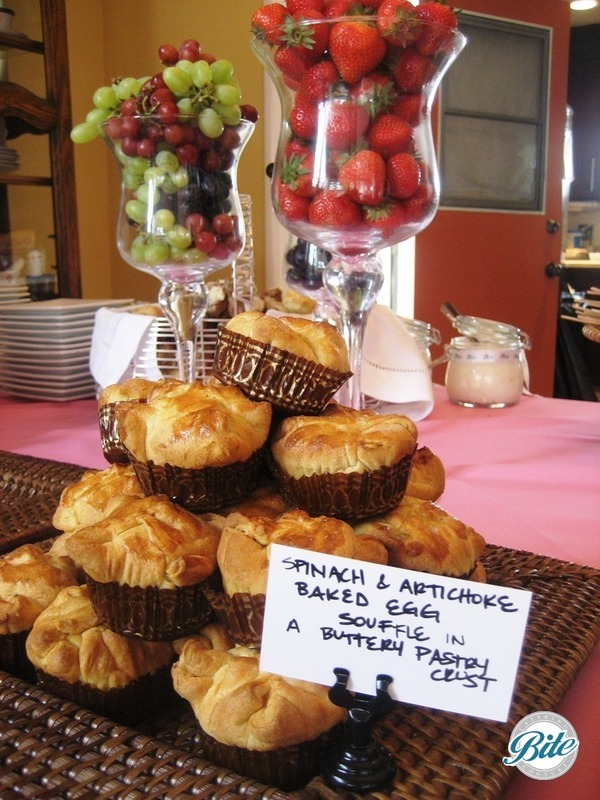 Spinach and artichoke baed egg souffle in a buttery pastry crust, shown with fresh fruit on stationary display
