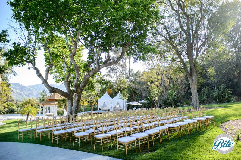 Lawn at Newhall mansion set up for wedding with chairs and tents.