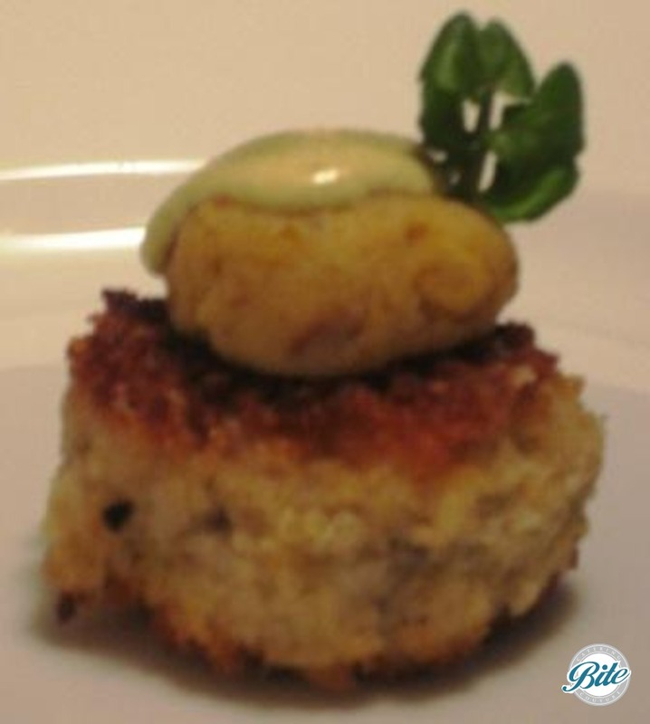 Crab cake bite with remoulade and micro green garnish