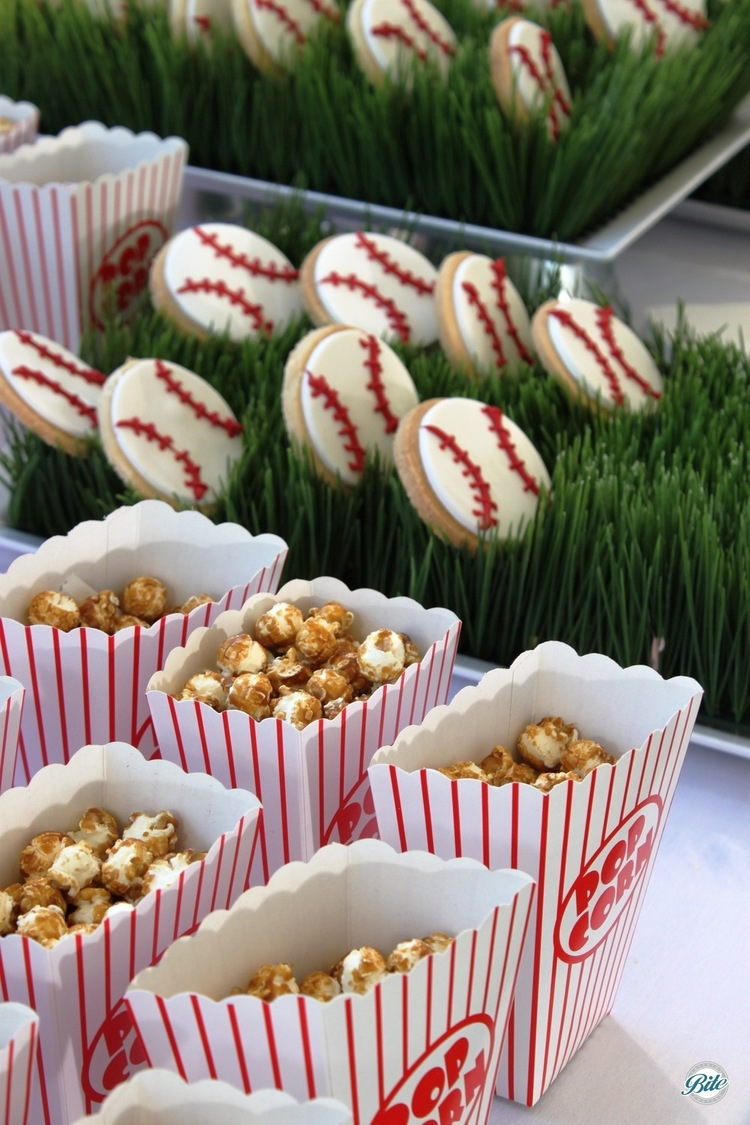 Baseball VIP tent snacks with kettle corn and baseball cookies on ball park style display