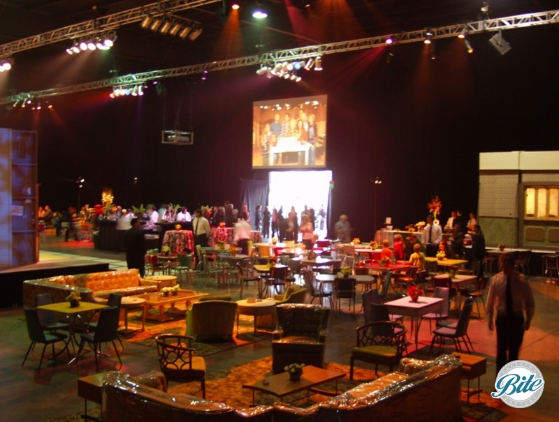Video screens with tables, chairs, and couches layout