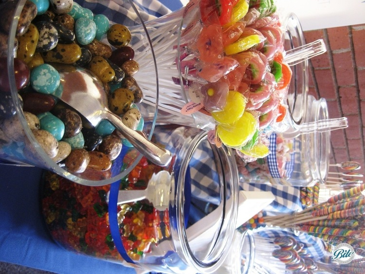 Candy display with assorted candies, including gummy bears, lollipops and jelly beans on country store themed display with gingham accents