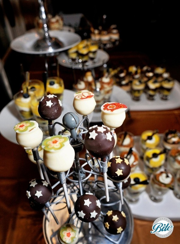 Cheesecake pops with chocolate and vanilla icing on dessert buffet