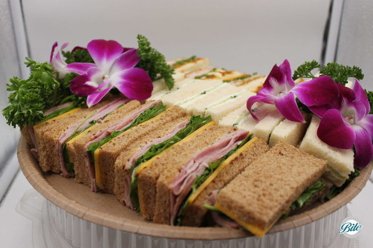 Assorted finger tea sandwiches including ham and cheddar, cucumber and boursin, and turkey with brie.  Garnished with fresh flowers