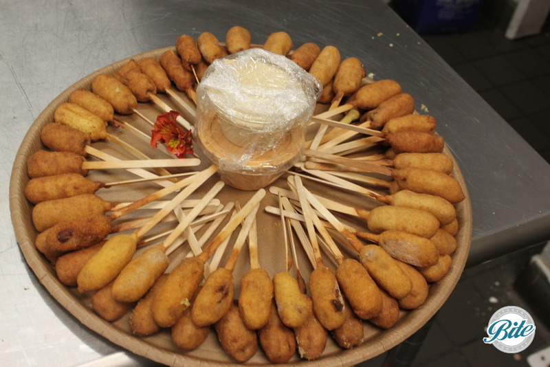 Mini corn dogs with honey mustard dipping sauce on to-go platter