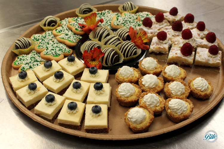 St. Patrick's day themed a la carte dessert assortment with whiskey brownie truffles, shamrock shortbread cookies, raspberry shortbread bites, cheesecake bars and mini citrus tarts