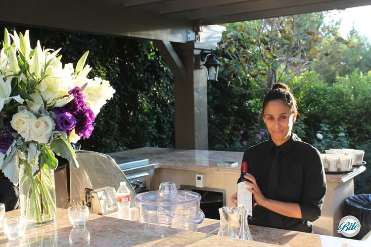 bar set up outdoors with fresh flowers, afternoon sun light and bartender serving drinks.