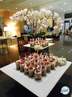 Chocolate dessert shots with fresh whipped cream and raspberries on display.