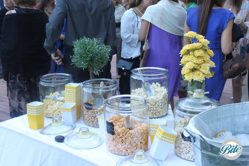 Popcorn display on outdoor set up with oversized jars, scoops and to go-cups for guests