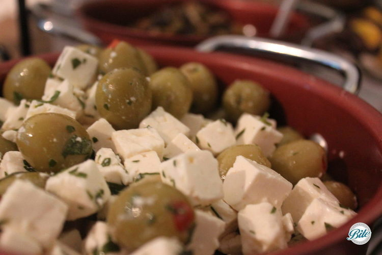 Marinated olives and feta with fresh herbs on Mediterranean display