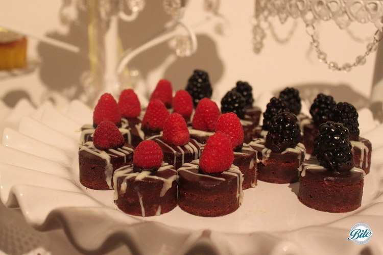 Chocolate mint bites with drizzled frosting and raspberry garnish on white dish