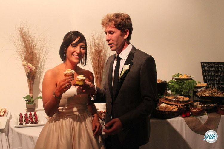 The newlyweds with their cupcake desserts instead of cake, cheers!