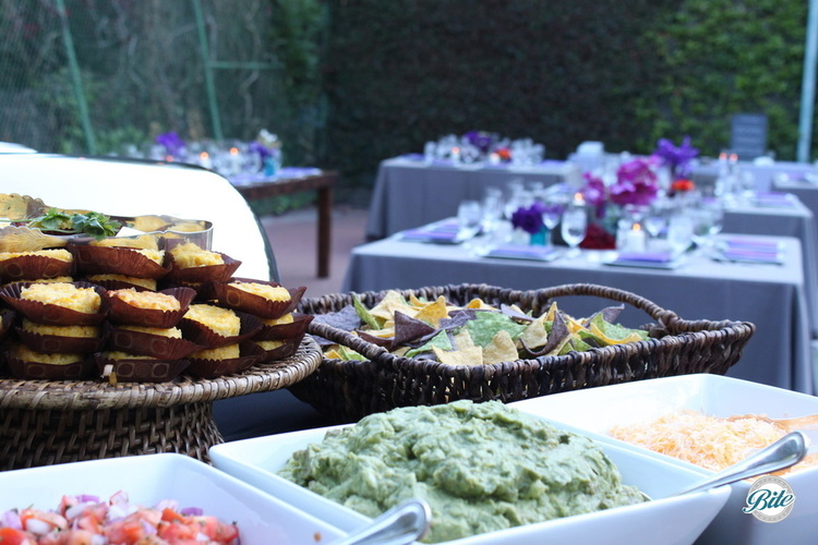 Mexican Taco Station with corn cakes, chips, guacamole, cheese and guacamole, guest reception seating shown in the distance