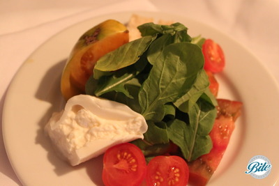 with burrata cheese, heirloom tomatoes, field greens and finished with balsamic vinaigrette