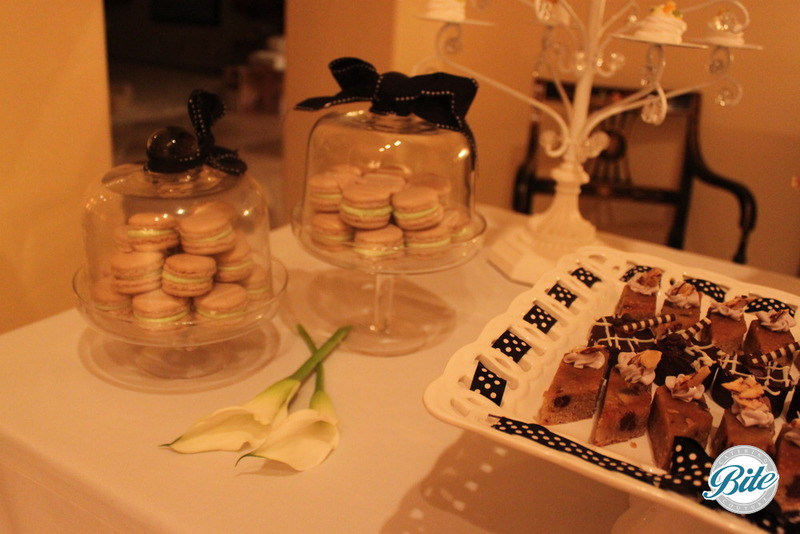 Macaron and blondies and brownies on a black and white dessert display