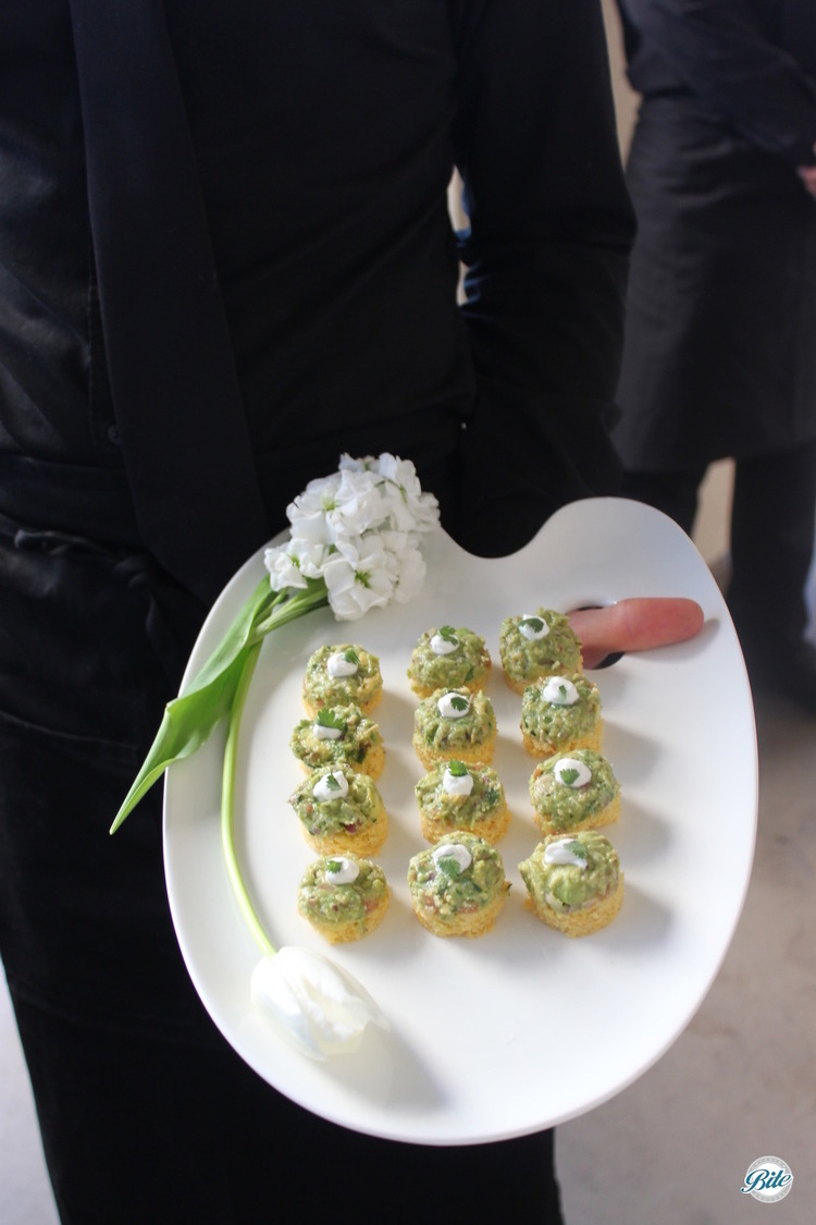 White tray filled with cornbread canapes.  Chicken, guacamole, crema, cilantro.