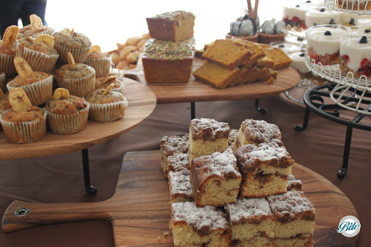 Coffee cake, banana nut cupcakes, pumpkin bread, and granola parfaits displayed at continental breakfast
