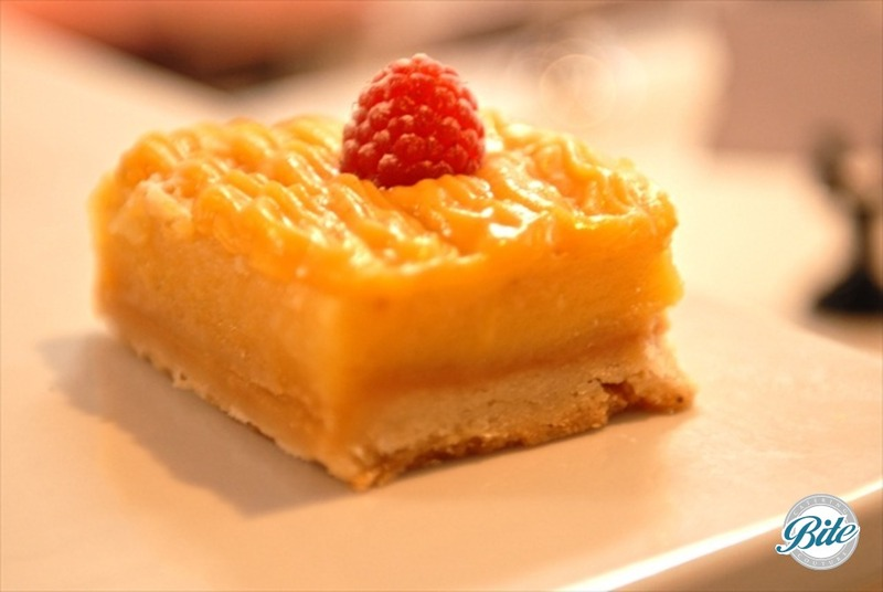 Summer lemon bar with buttery crust, lemon curd filling and raspberry garnish