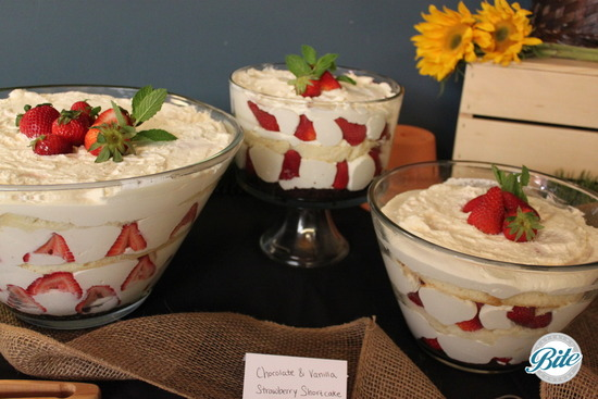 Vanilla Cake, whipped cream, vanilla custard and strawberries served on rustic display with fresh flowers, burlap and wood crates