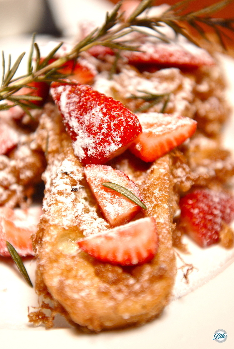 Plated with strawberry and powdered sugar, served with Canadian maple syrup, and garnished with fresh rosemary