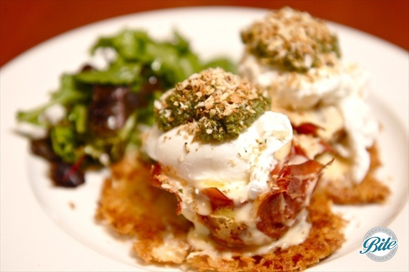 Potato latke, prosciutto cup, cheese and egg custard, poached egg pest crumble and field greens.
