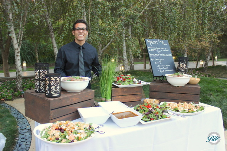 Market salad station  with multiple salads staffed by server in black bistro