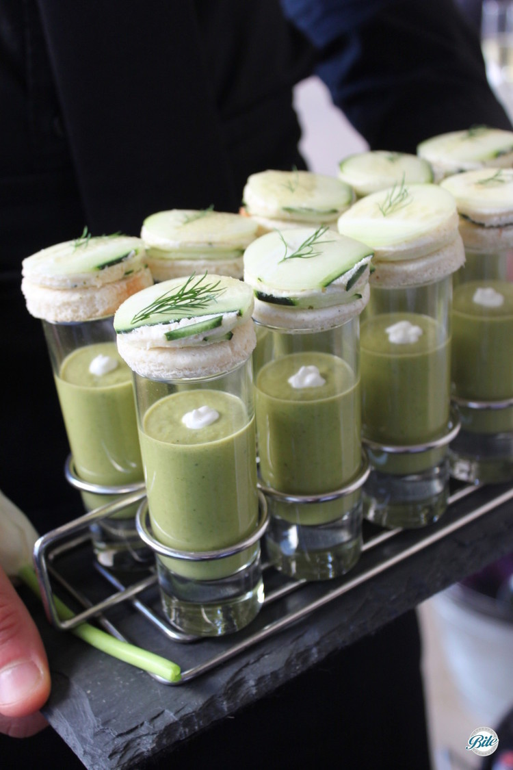 Sweet pea soup shooter with mini cucumber and boursin sandwich, served tray passed on slate.