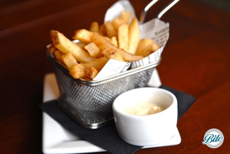 Truffle fries served in a wire basket with a side of aioli