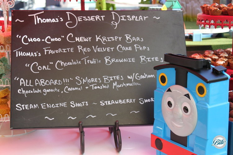 Custom chalkboard menu with Thomas the train truck, choo choo chewy krispy bars, coal chocolate truffle brownie bites, all aboard s'mores bites, and steam engine shots with strawberry s'mores