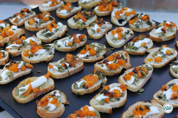 Roasted pumpkin crostini with pumpkin seeds on black tray