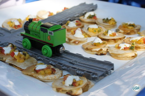 Mini veggie quesadillas with sour cream and tropical salsa on train themed display