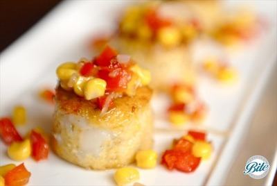 Sauteed shrimp and grits cakes served with corn succotash