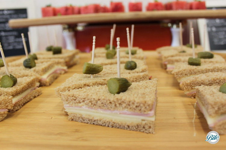 Tea sandwich with deli pickle garnish on stationary display